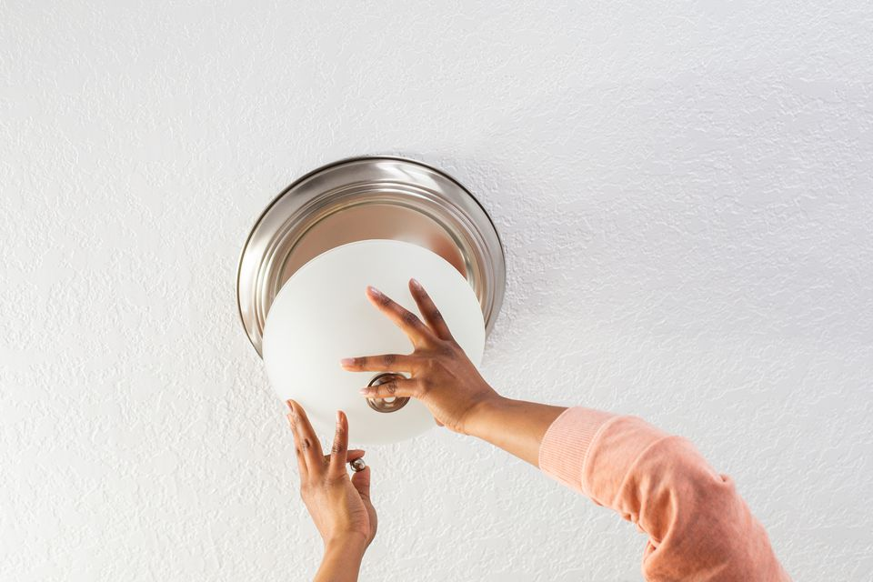 person removing a light fixture dish