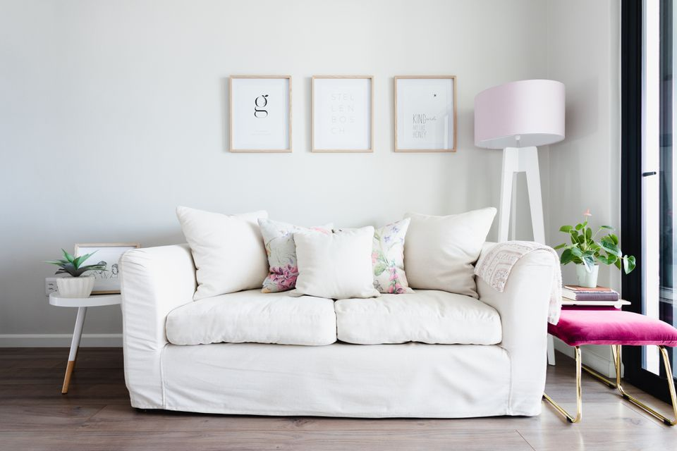 White couch with puffy cushions in middle of decorated living room