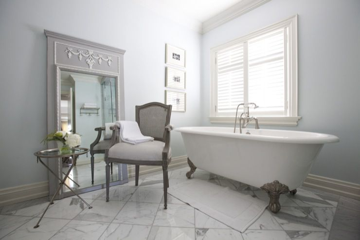 Grey and white bathroom with claw-foot tub and sitting chair.