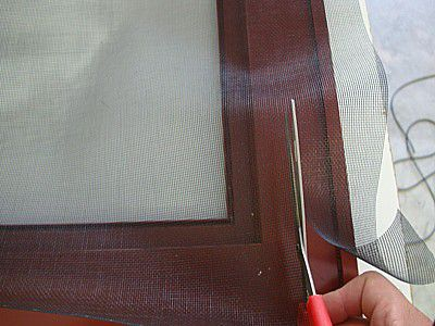 Trimming excess screen material with scissors