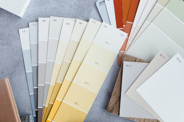 Various paint sample cards laid out on blue surface