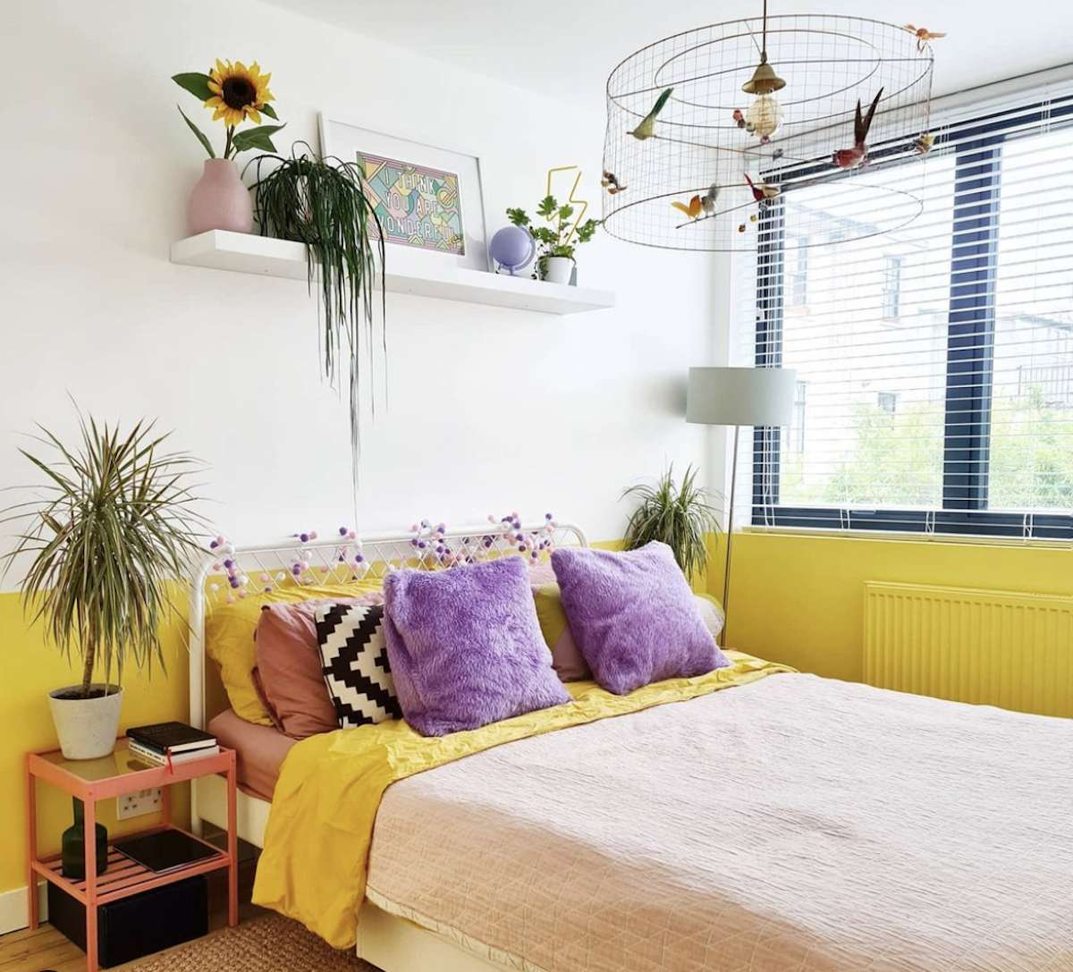 purple and yellow bedroom with white walls, floating shelf with plants and artwork, chandelier that looks like a birds cage