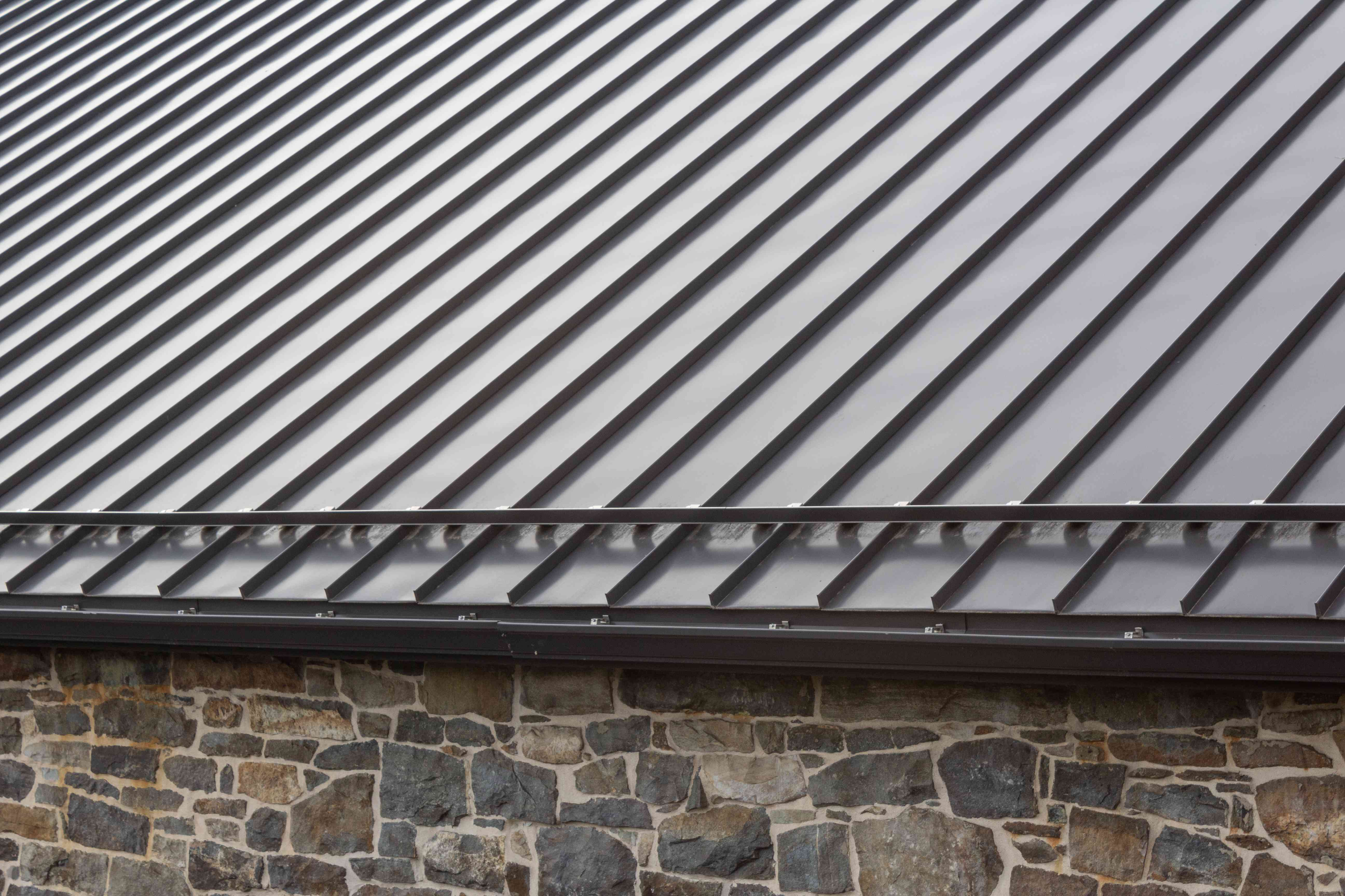 Standing seam modern metal roof over vintage stone wall