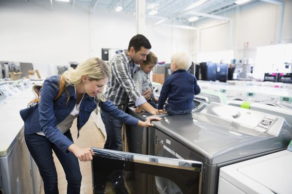 Young family shopping for clothes washer in appliance store