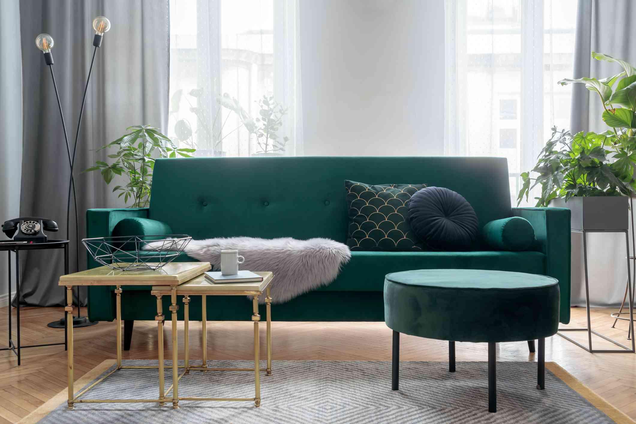 sofá verde en la sala de estar con una alfombra  , flores frescas en un jarrón sobre una mesa en la sala de estar