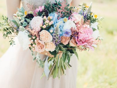 bride's hands hold beautiful bridal bouquet of peony. fine art photography.