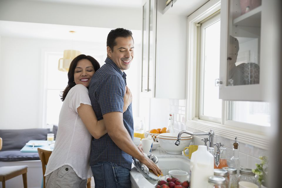 Affectionate brunette couple hugging at kitchen sink