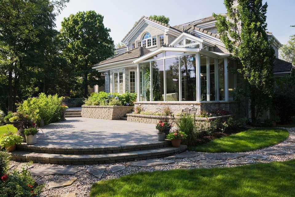 Casa de estilo cabaña de ladrillo y piedra con terraza acristalada, patio y patio ajardinado, Quebec, Canadá