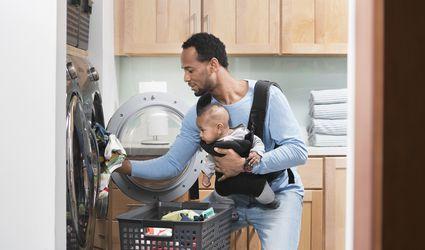 man and baby putting laundry in washing machine