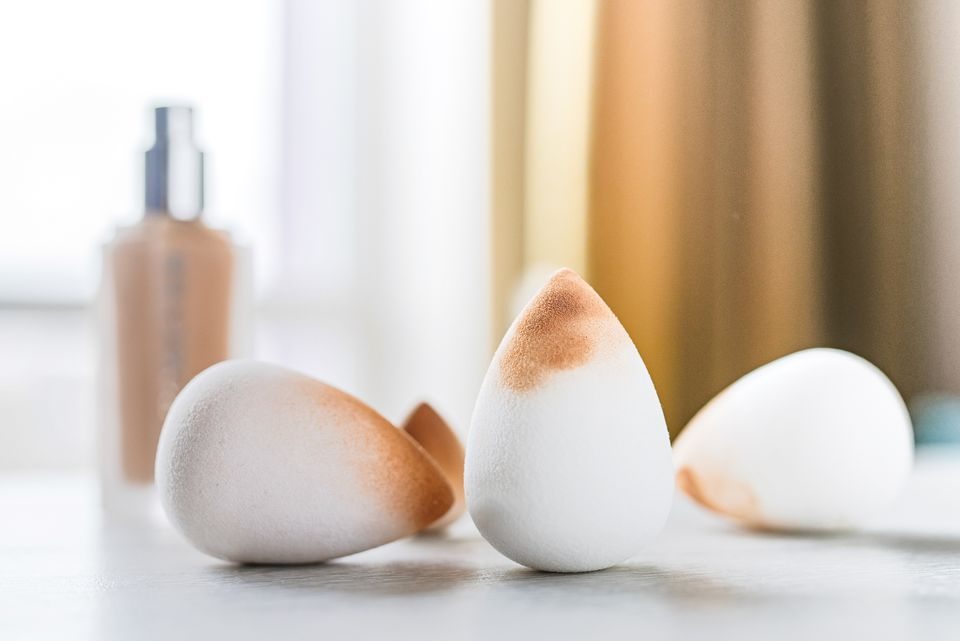 White cone-shaped beauty blenders with makeup in front of foundation bottle
