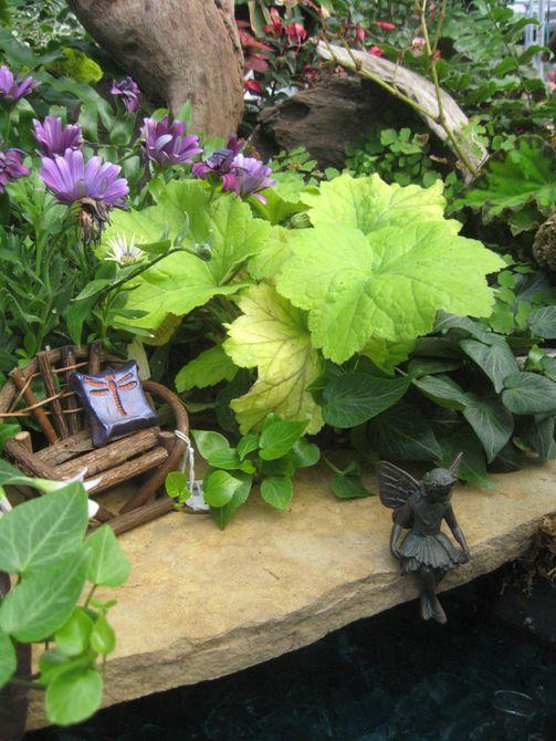 Banco en miniatura y estatua de hadas entre plantas