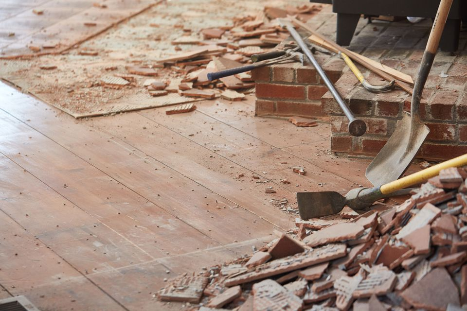 Bricks broken and scattered across wood floor with tools for home renovation