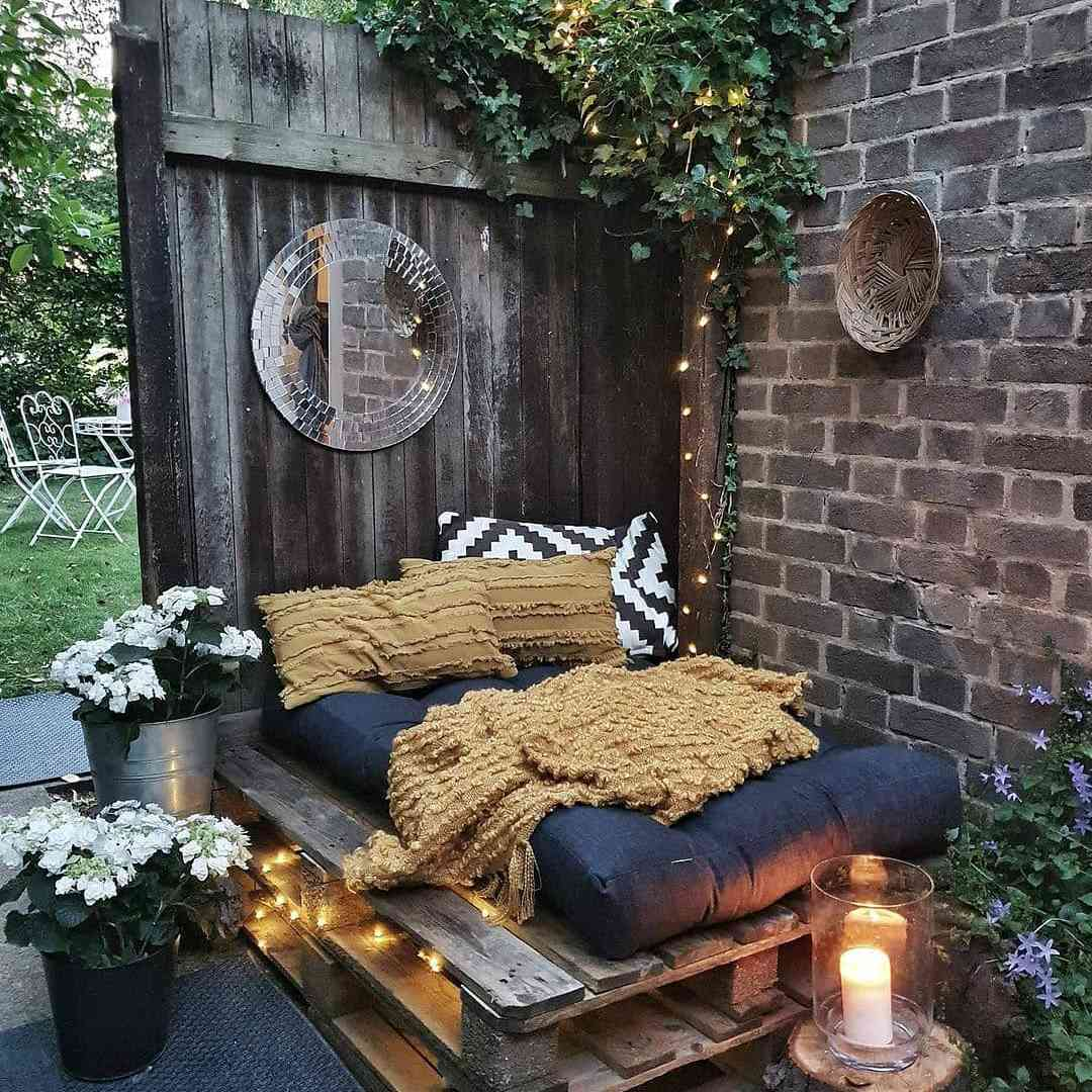A napping nook in a yard with a wood pallet bed and bedding.