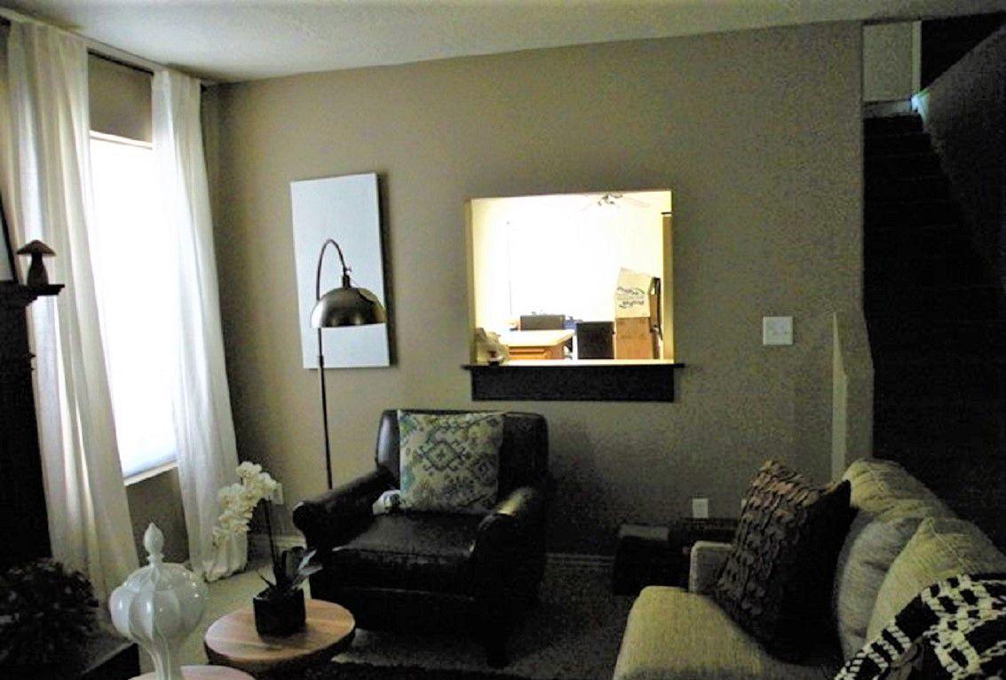 Sala de estar oscura y lúgubre con silla de cuero, lámpara y sofá antes del cambio de imagen
