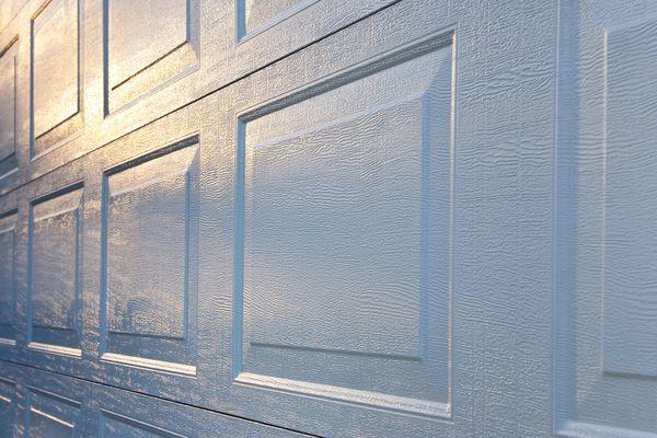 New Aluminum Garage Door Background; Textured Surface Reflecting Sunrise