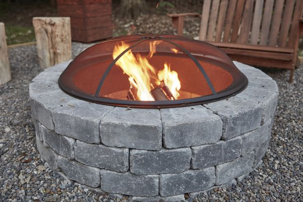 Circular firepit made of gray stones with protective cover on top of fire