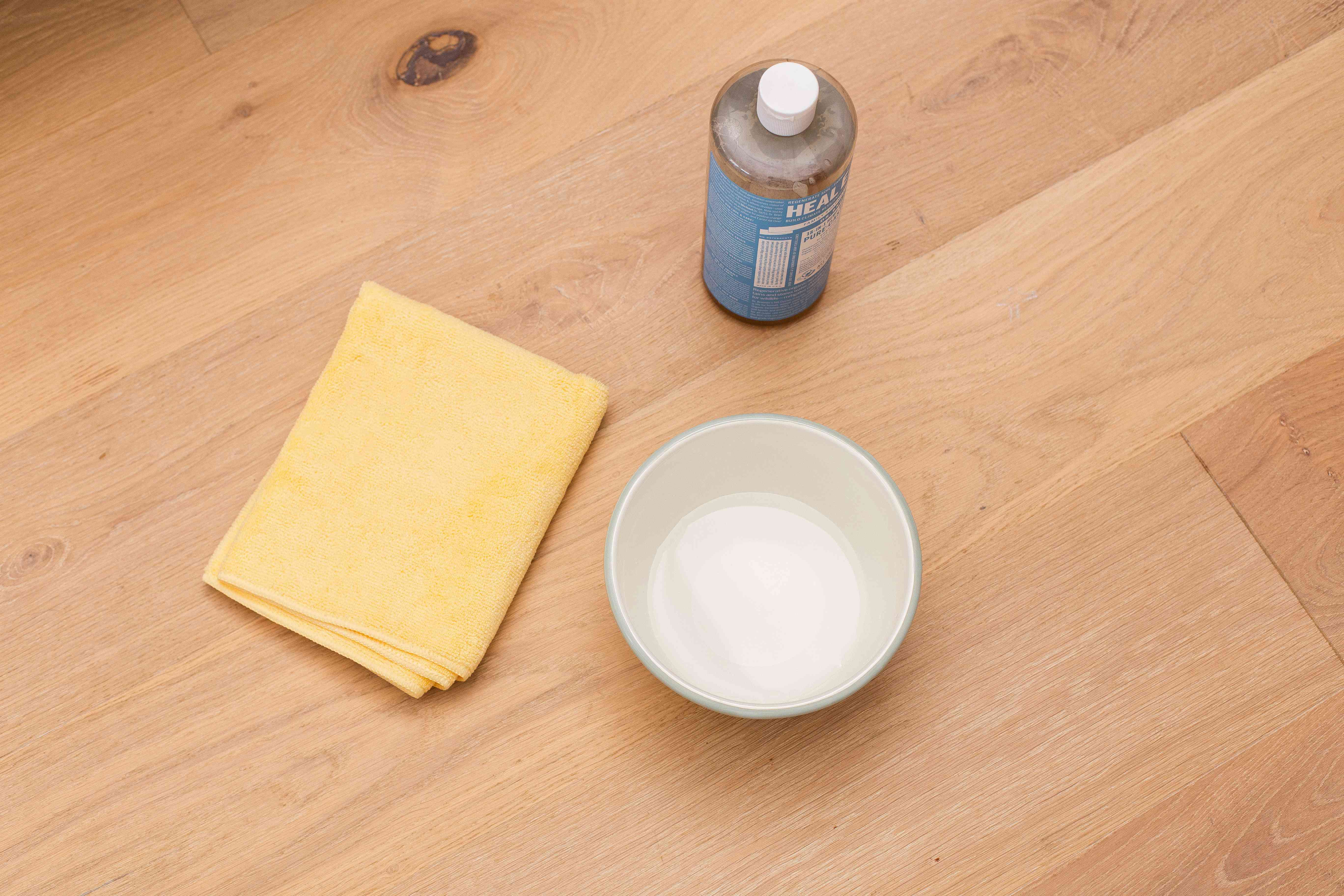 Mild soap bottle next to microfiber cloth and bowl of water for cleaning solution