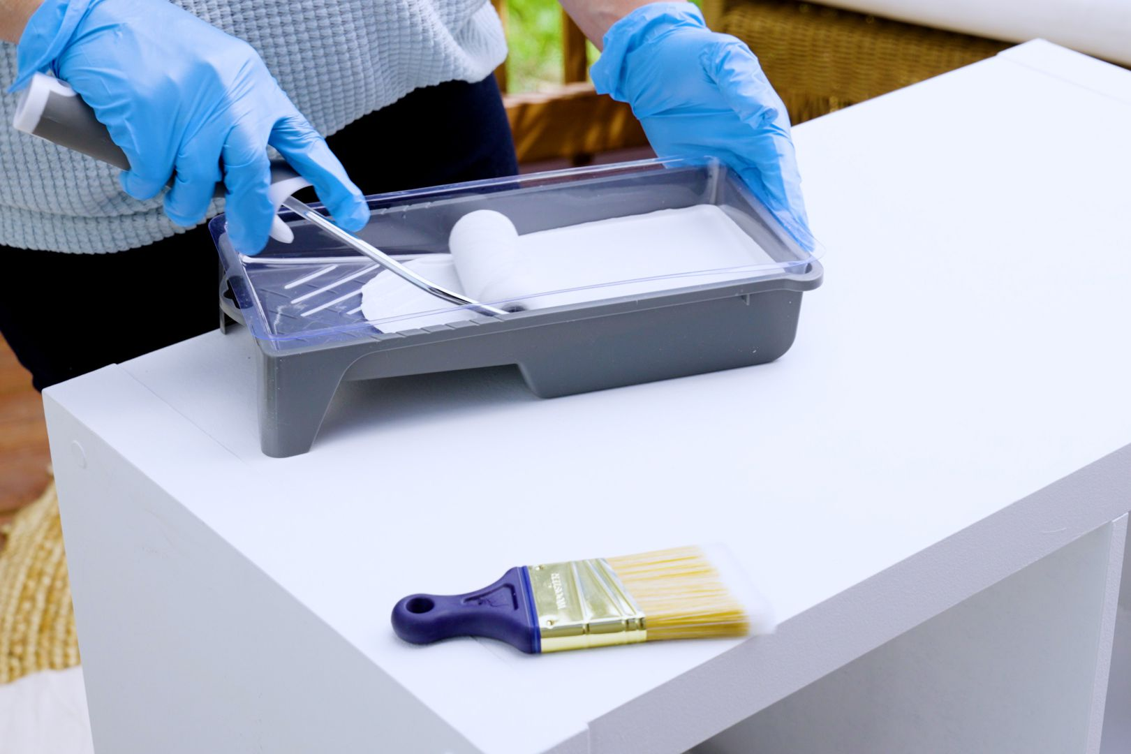 Painting tray with white paint and roller brush and flat brush on parrticleboard furniture