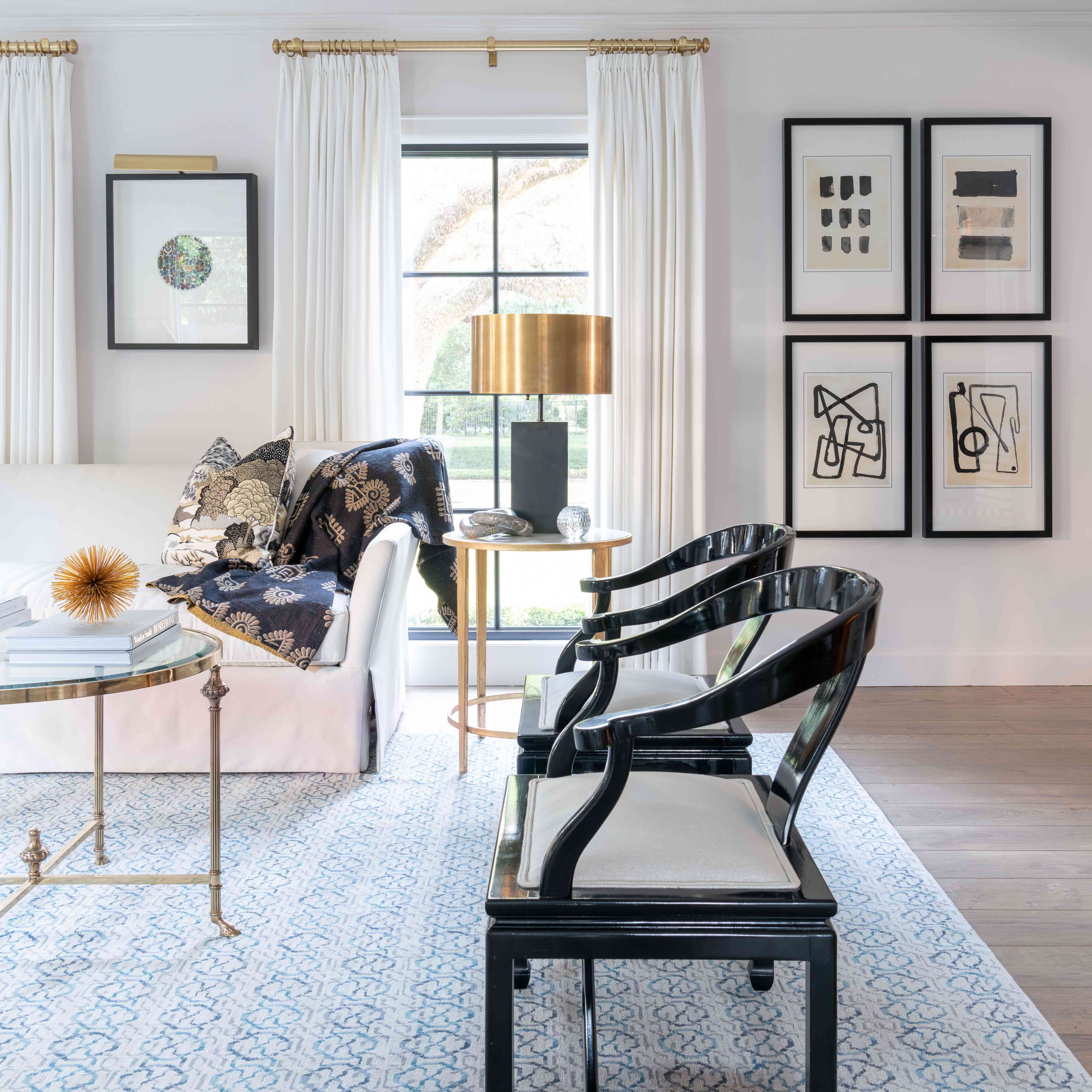 black accent chairs adorn this living room with minimalist, abstract art
