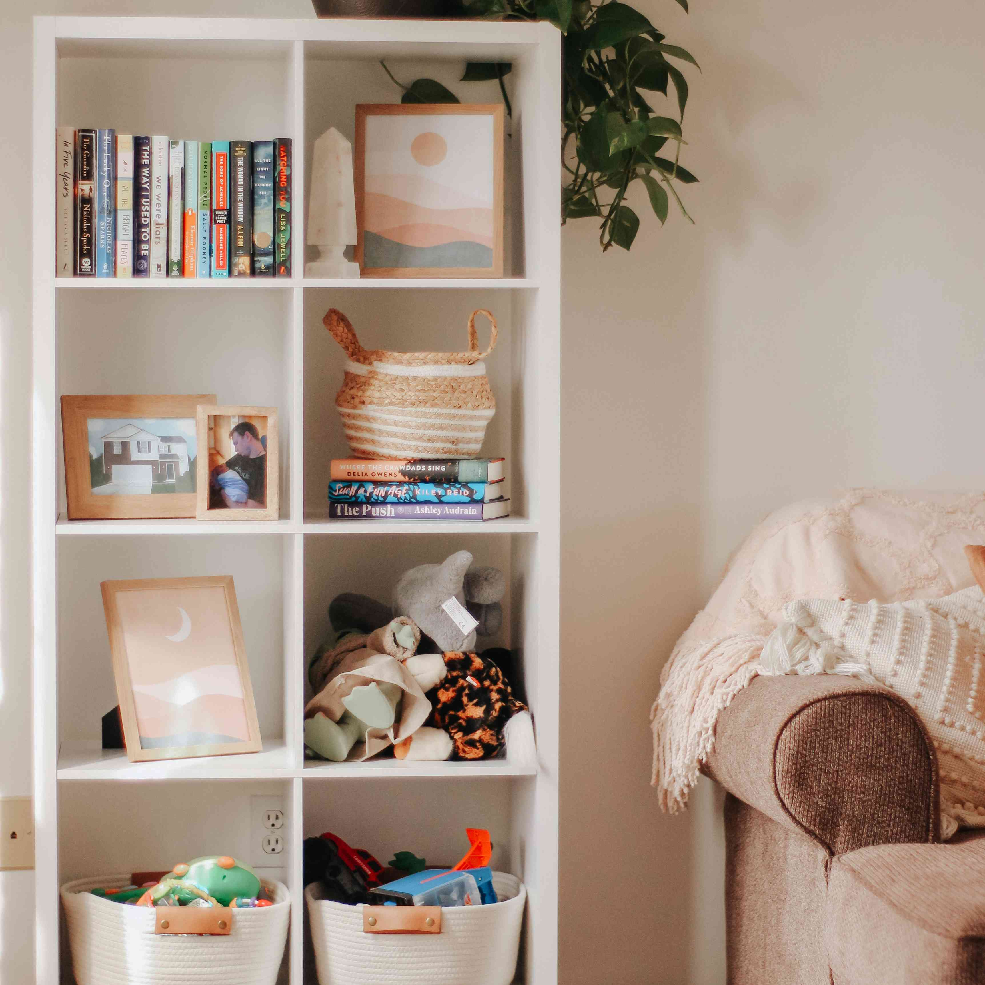 White bookcase with wooden legs showing off art and toddler toys