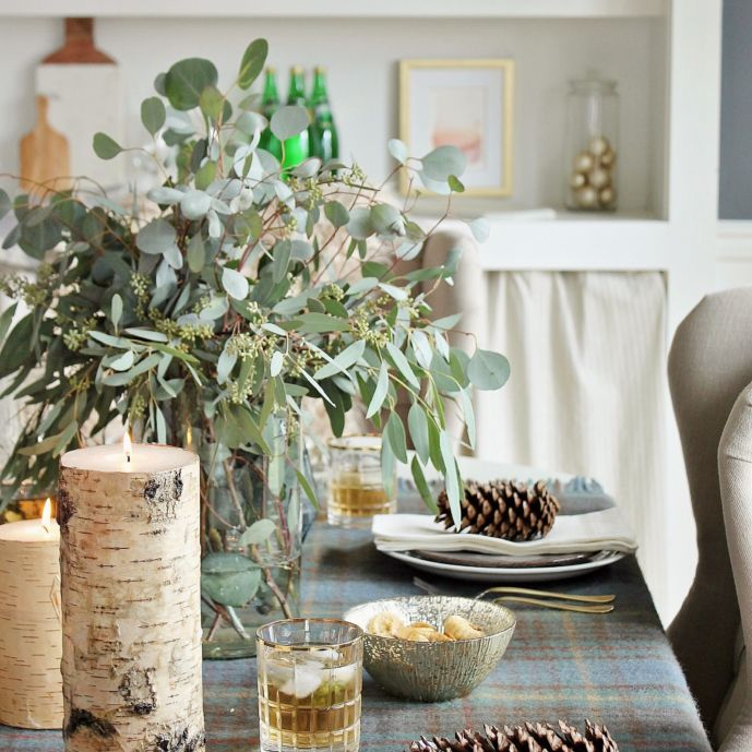 Table setting with pine cones on the folded napkins atop dinner plates.