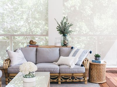 Outdoor living room decorated with brown wicker and gray couch, throw pillows and houseplants