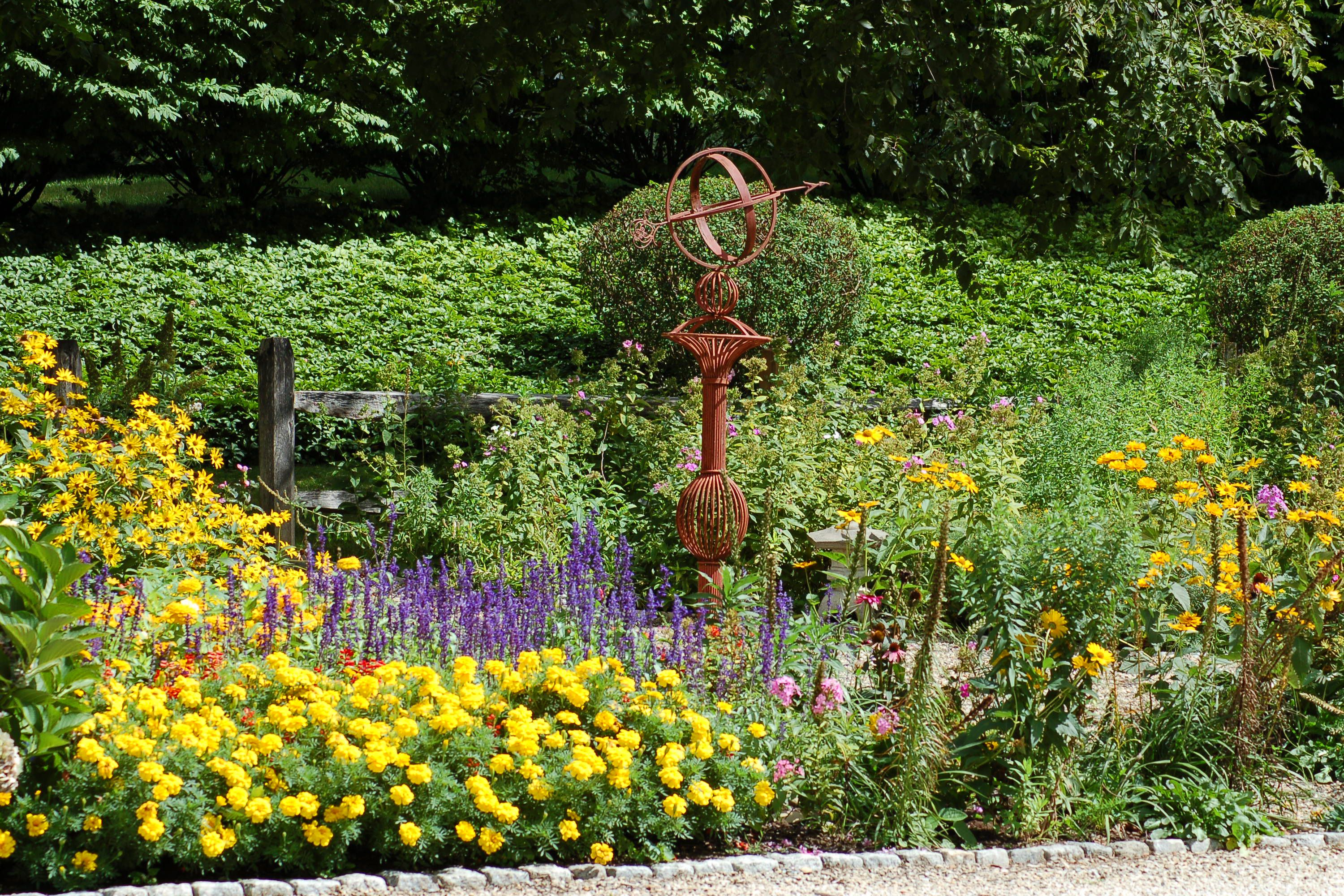 A flower border with lots of interest. It even has garden art.