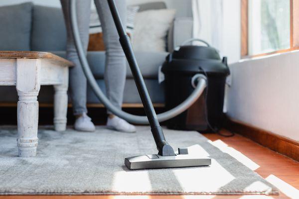 Upright vacuum cleaner vacuuming over carpet