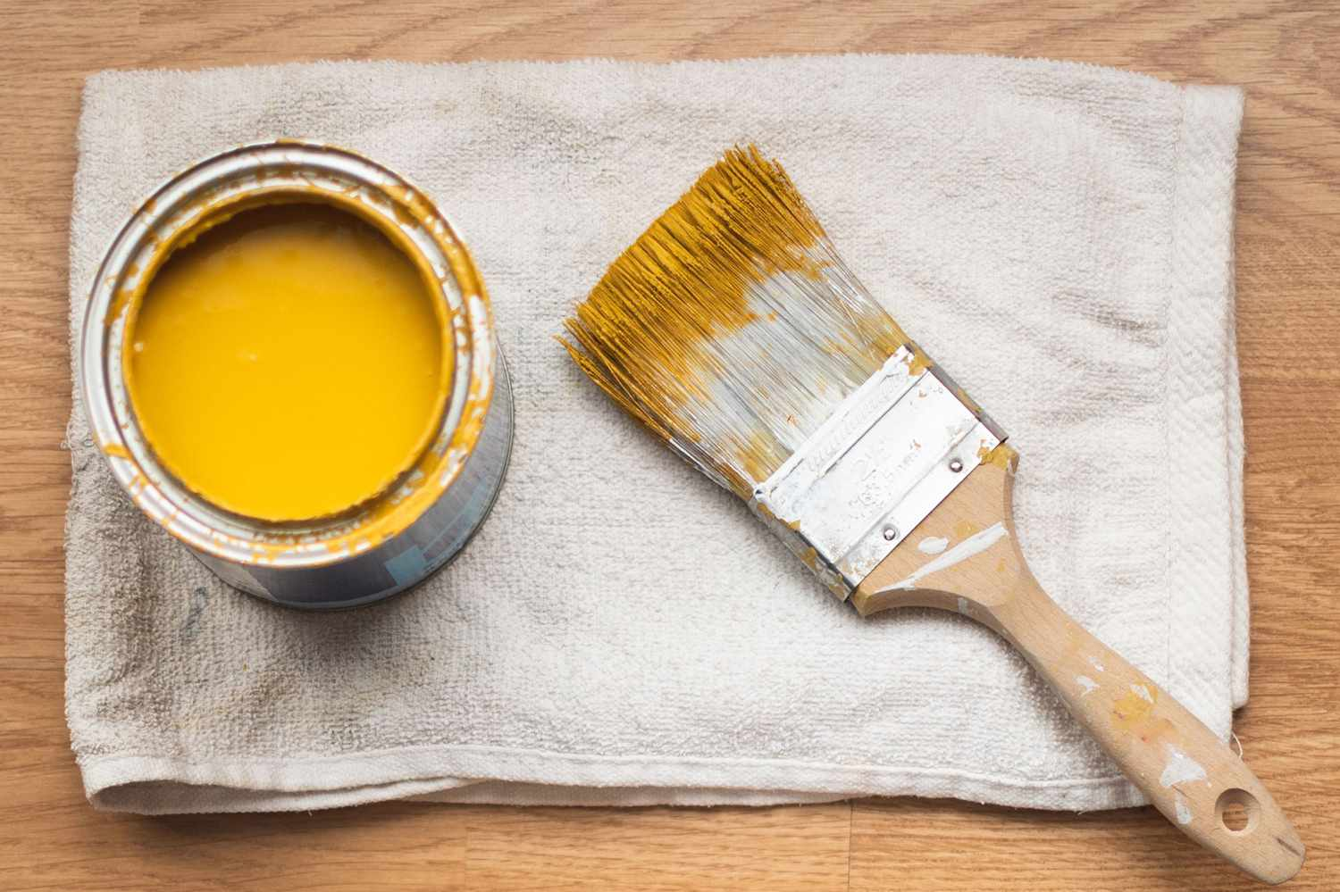 Paint bucket with yellow paint and paintbrush on white rag