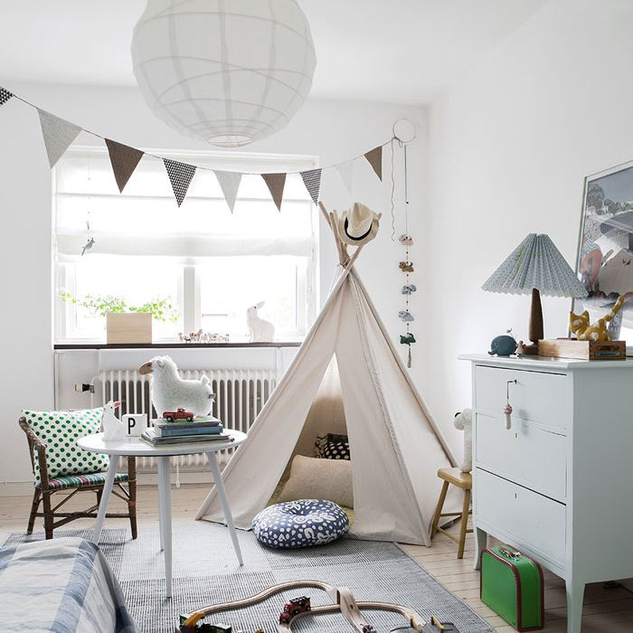 Bright and airy nursery with dramatic light fixture, large windows, and lots of natural light