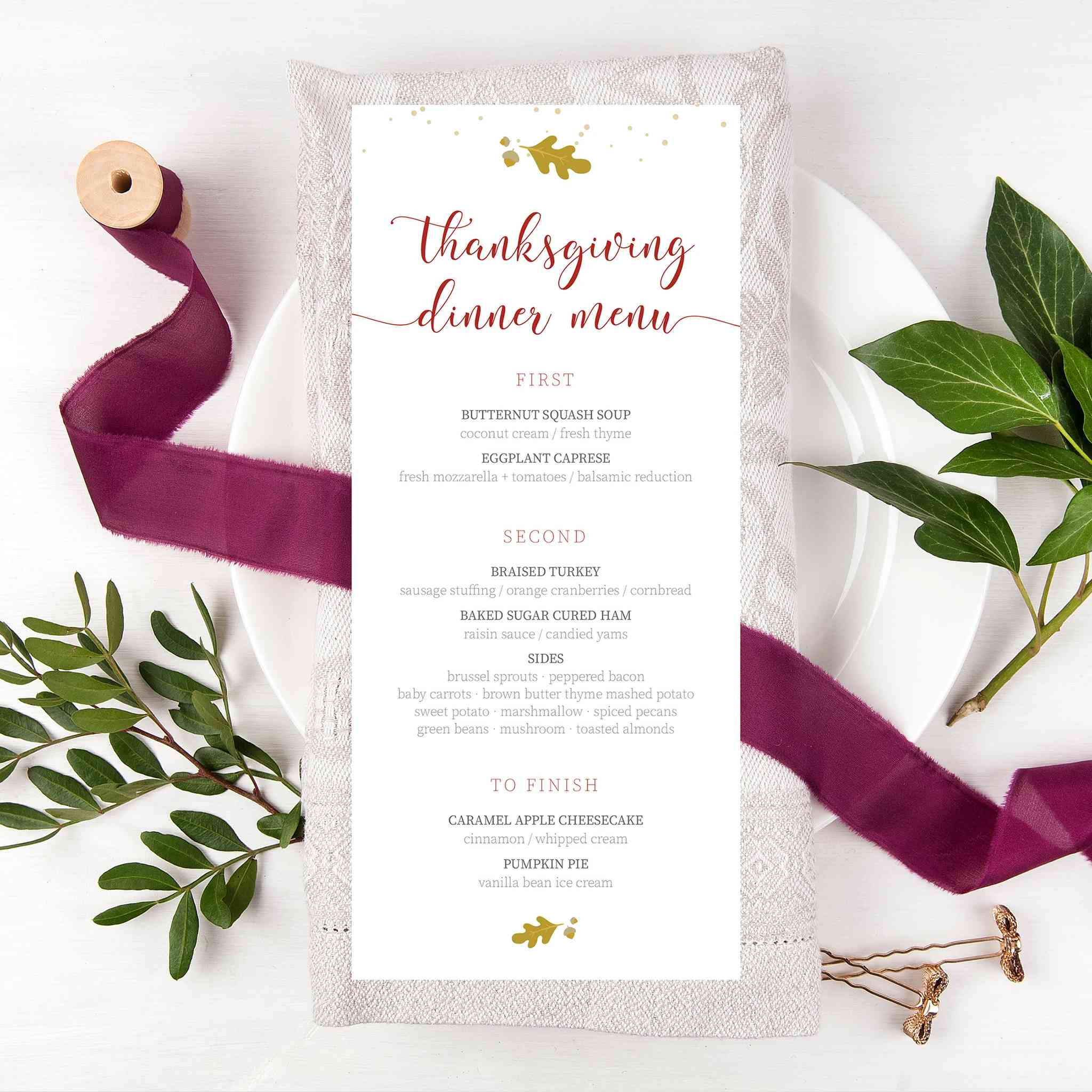 A Thanksgiving menu laying on a plate with ribbon and greenery