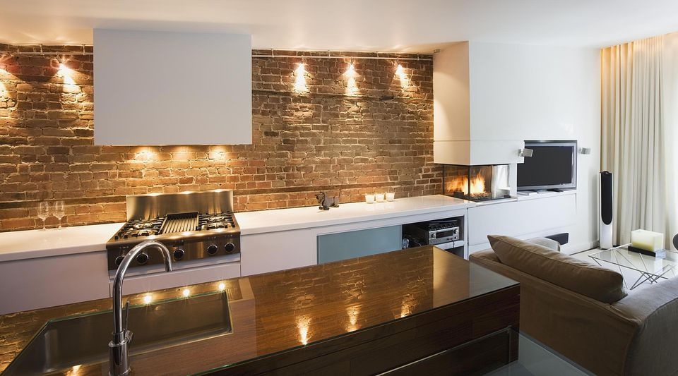 Modern apartment kitchen with exposed brick.
