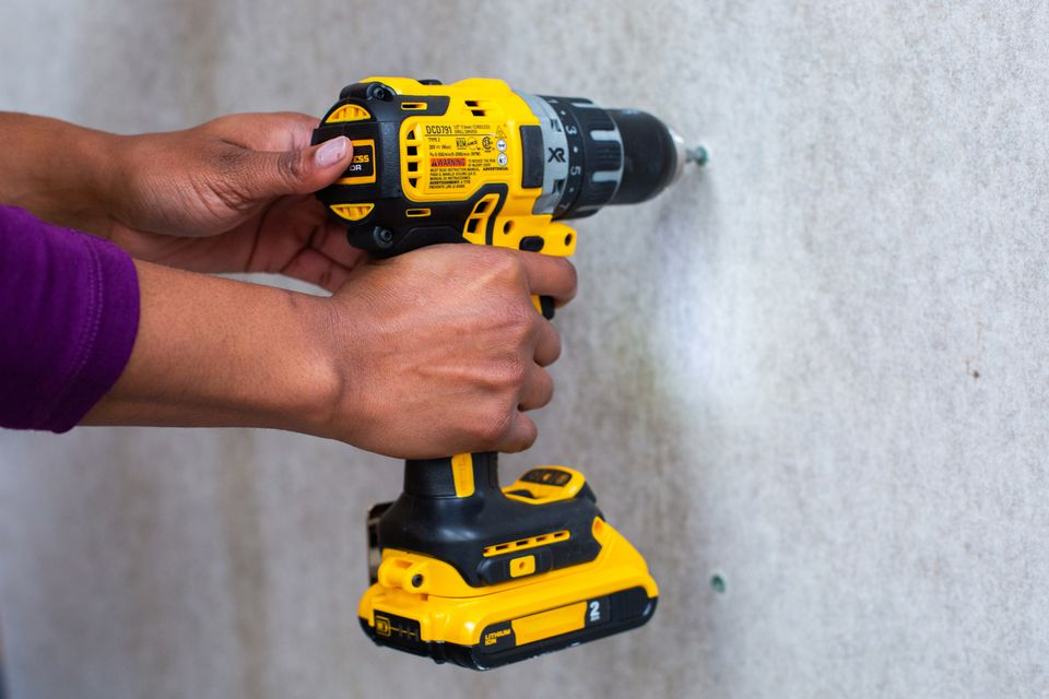 Yellow electric drill installing cement board