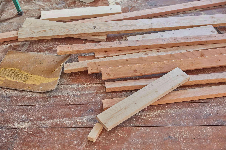 Pile of wooden planks and debris on floor post-demolition