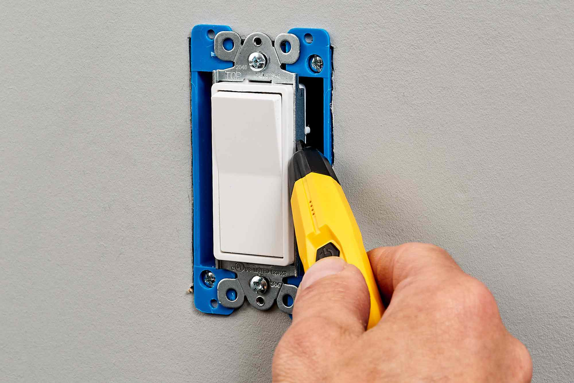 Yellow non-contact voltage tester testing light switch