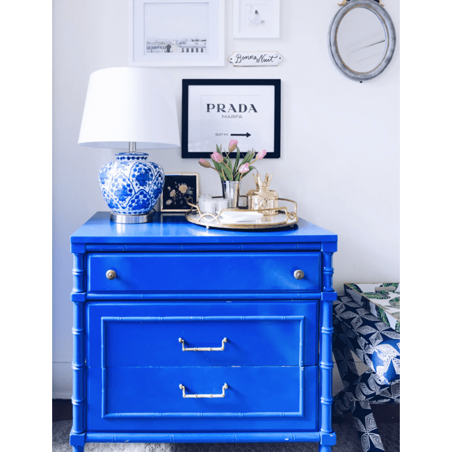 Sarah Lyon's blue chest of drawers features a round platter, blue lamp and art on the wall