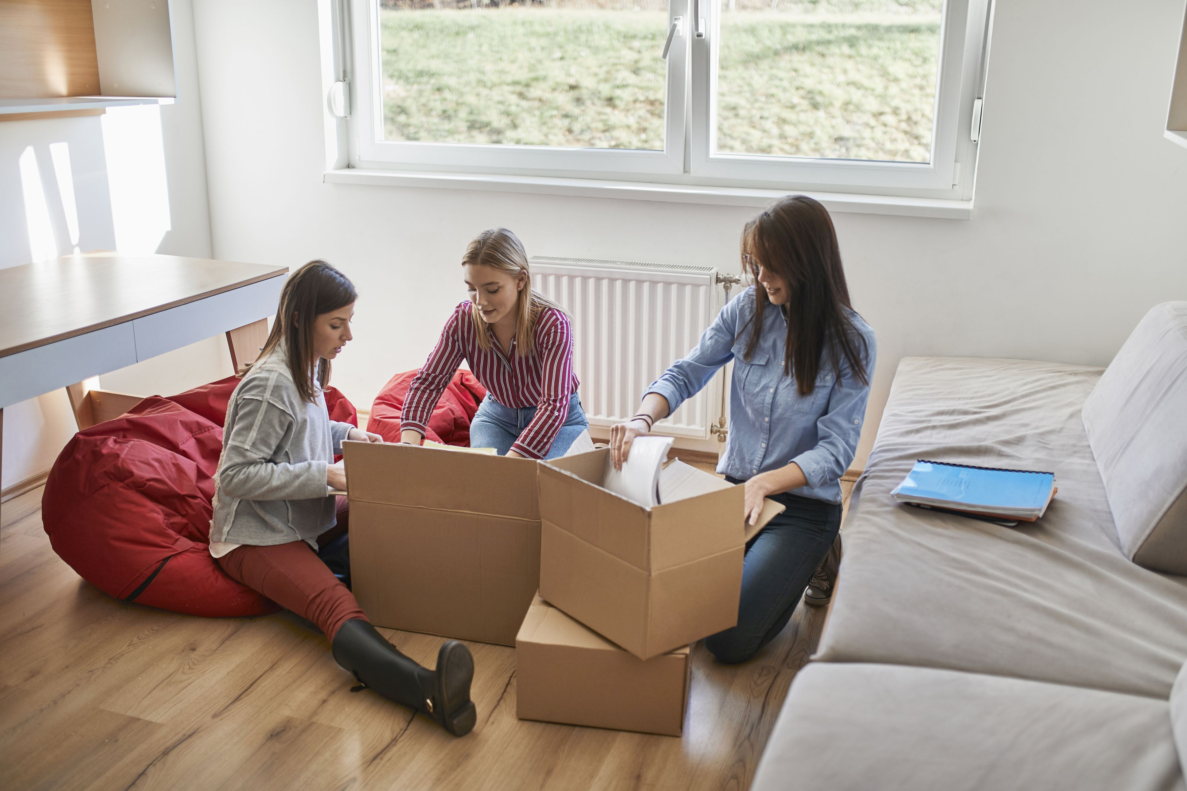 Three young women unpacking cardboard boxes in a room