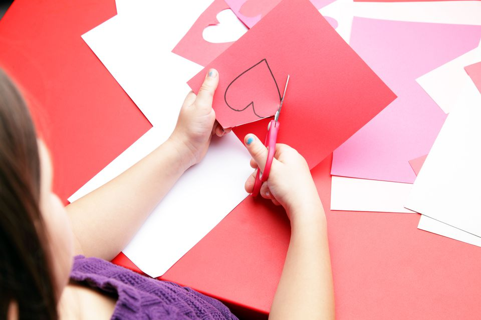 Girl cutting out heart shapes on red construction paper.