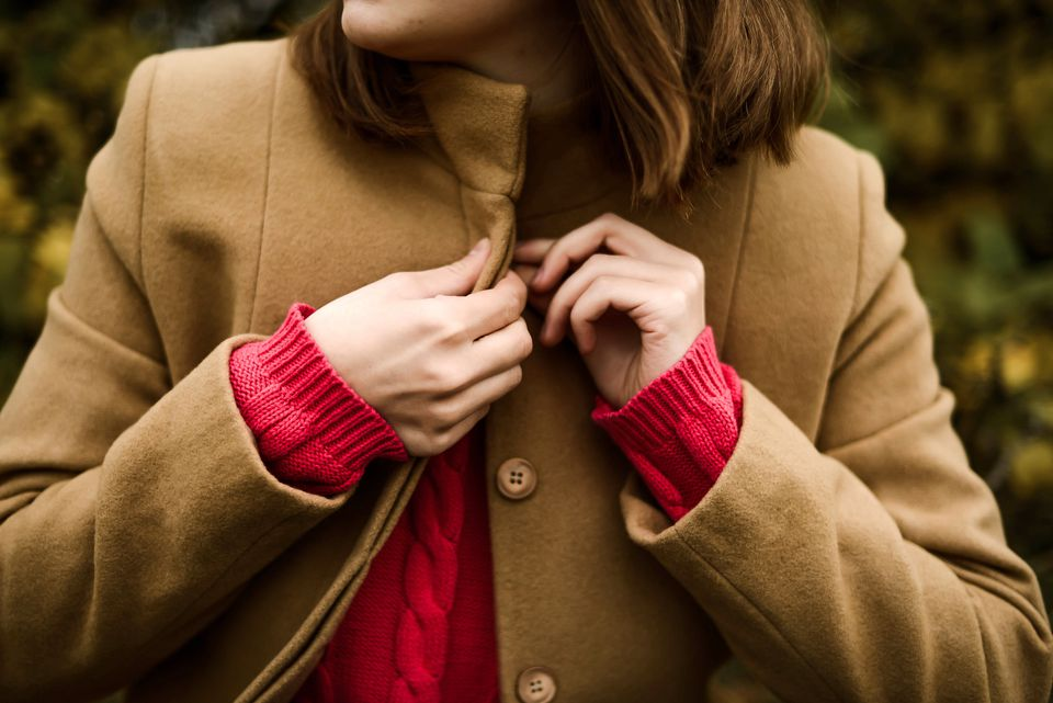 Woman buttoning a camel-colored coat