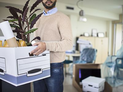 Businessman carrying crate in new office