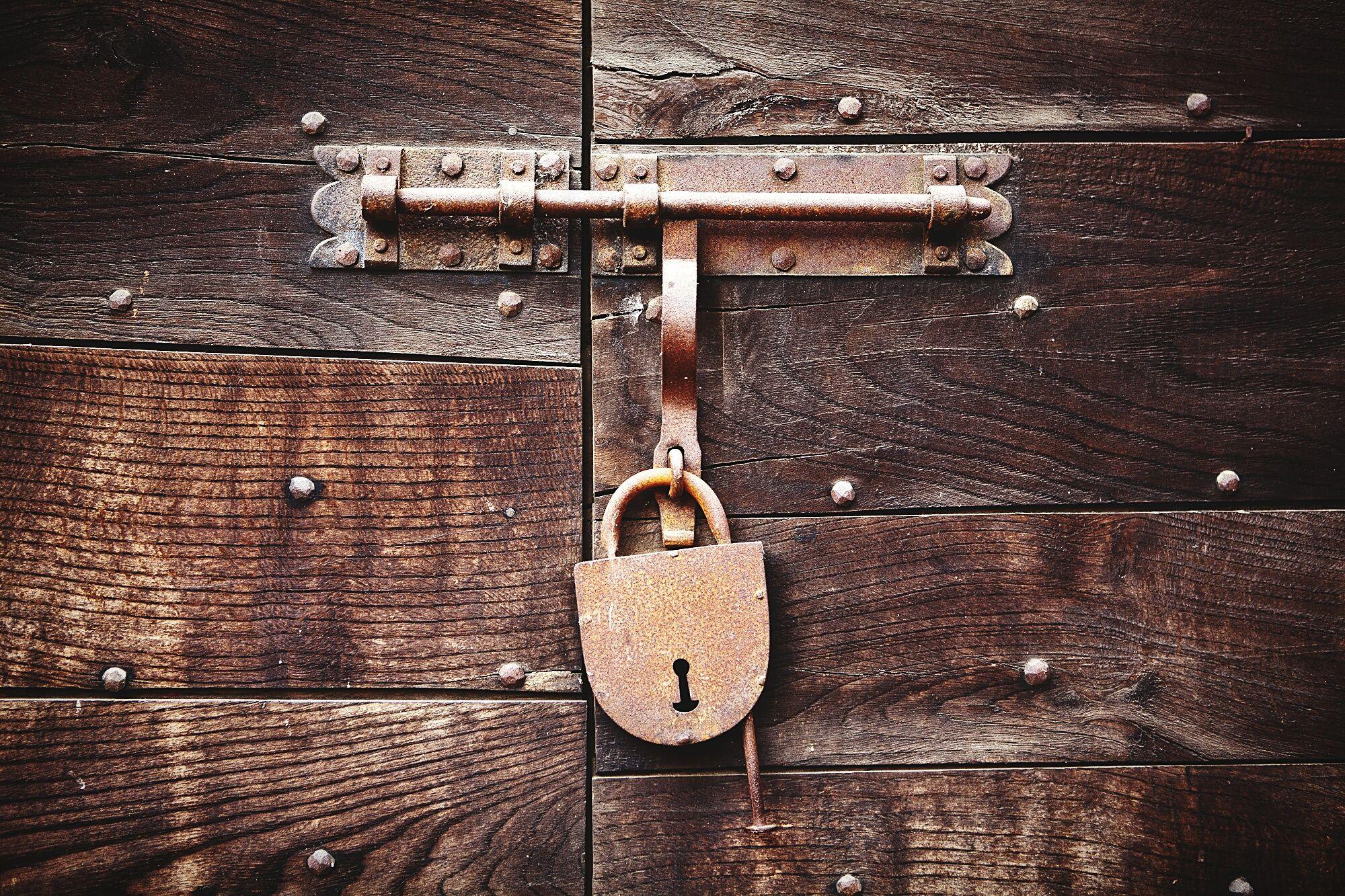Close-Up Of Rusty Lock On Wooden Door