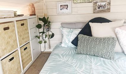 A tiny home bedroom with white wood paneling, aqua palm duvet, and baskets