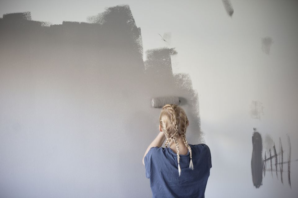 Woman rolling gray paint onto a white wall