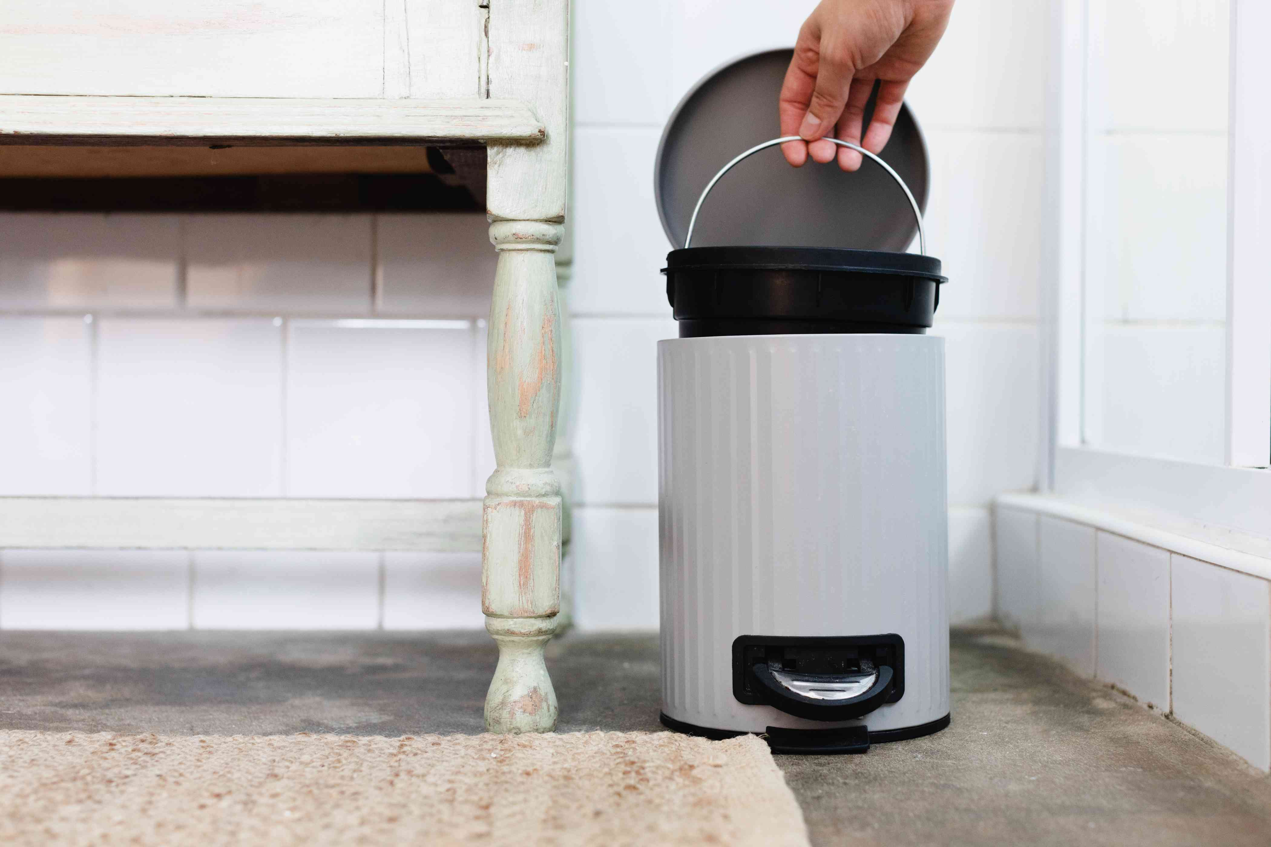 Bathroom trash can being lifted to removed bathroom odors