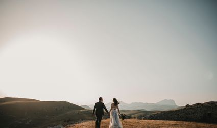 A newlywed couple hold hands and walk towards the horizon of mountains
