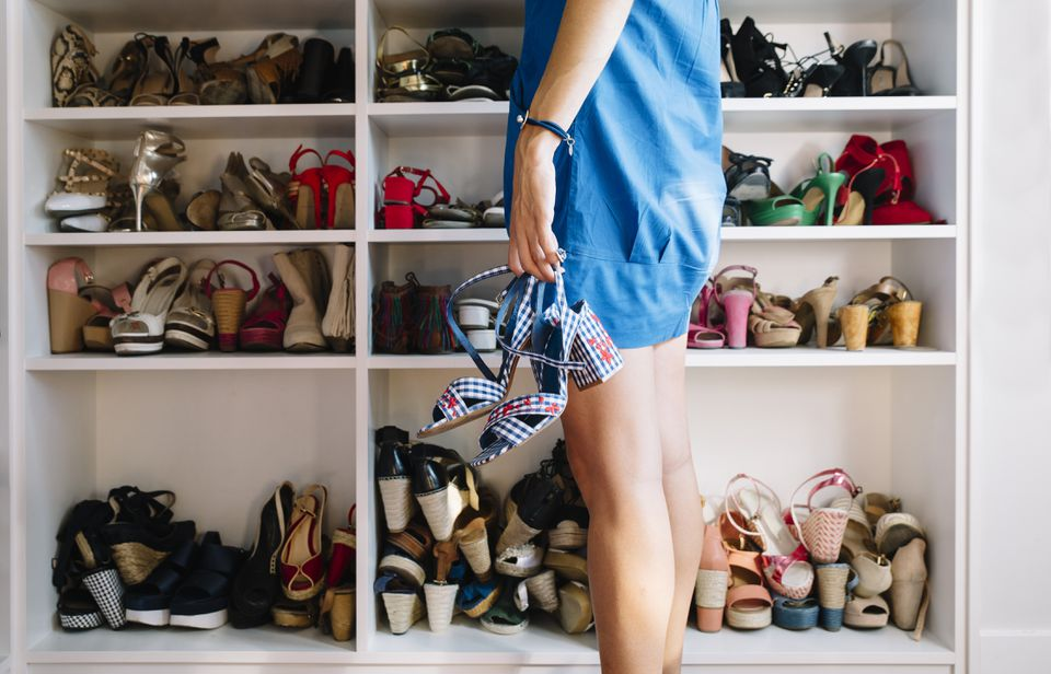 Woman with the shoes in the hand and Woman's shoes in the rack