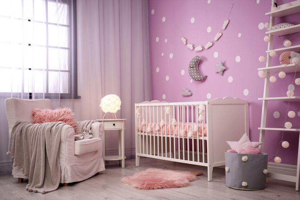 Interior de la habitación del bebé con cuna cerca de la pared de color
