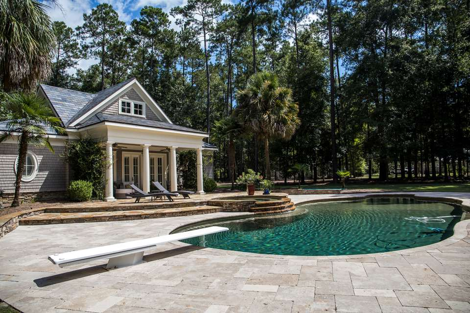 Custom pool House behind a landscaped estate with a large swimming pool and hot tub