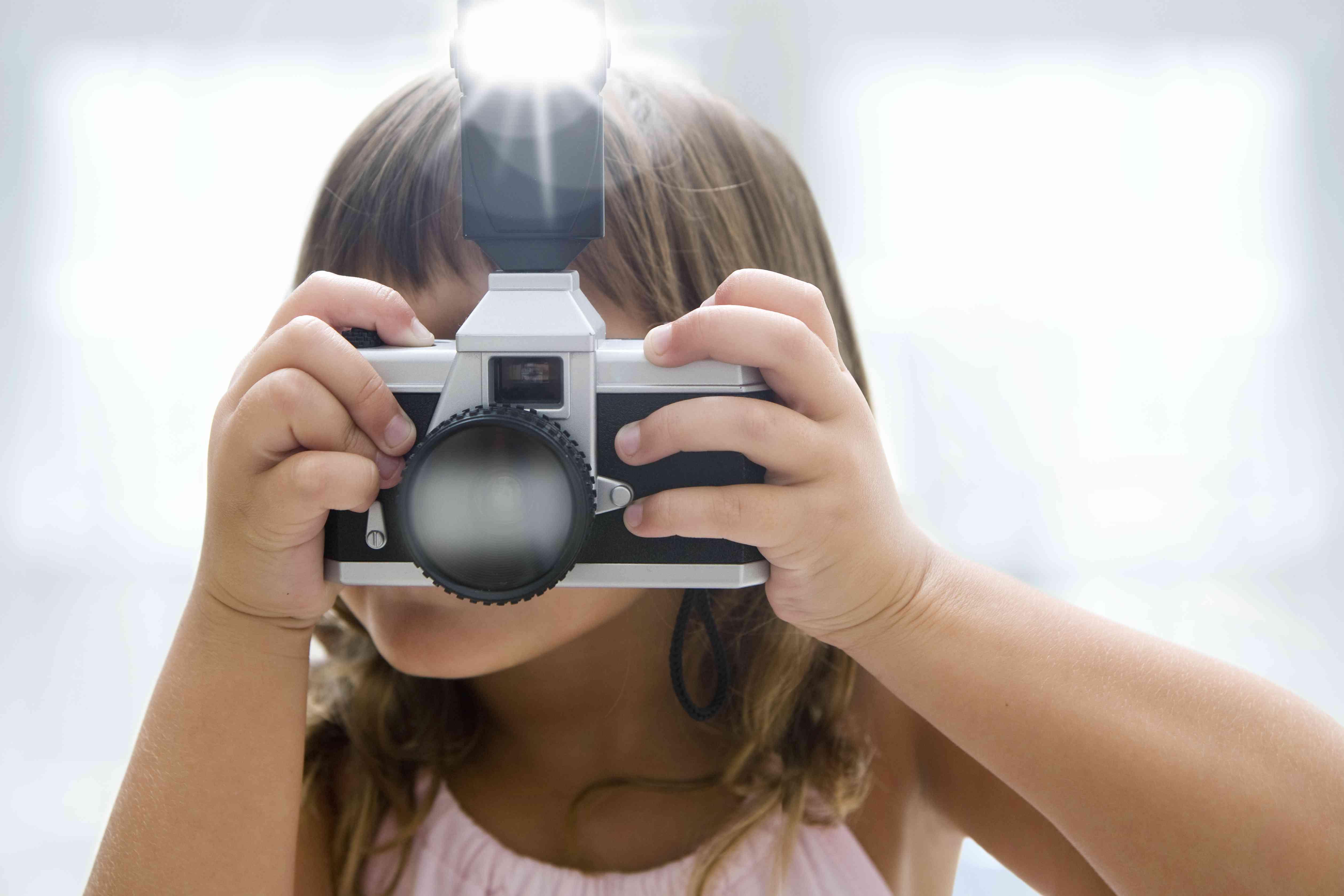 Girl using toy camera