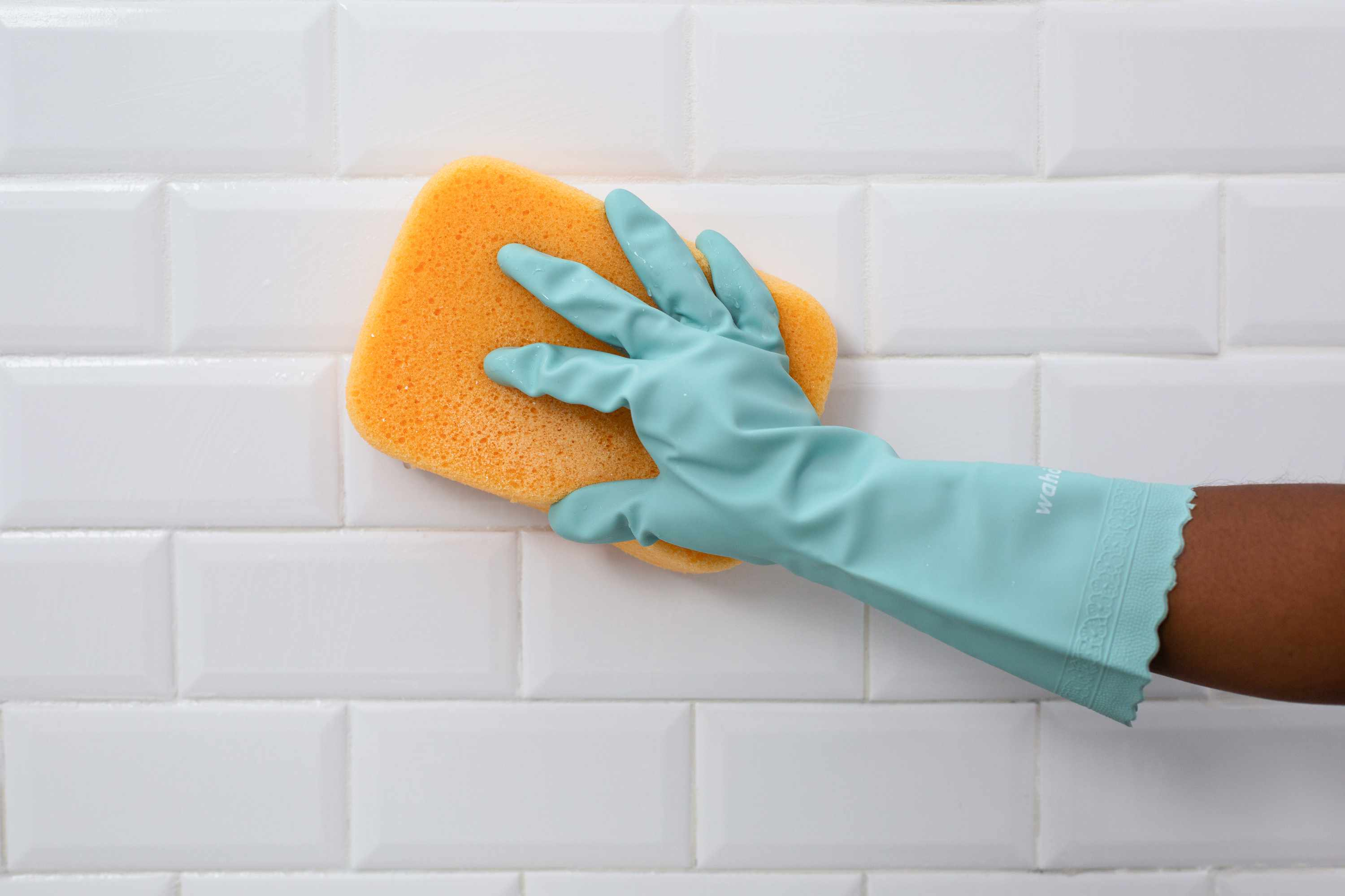 White tiled wall rinsed off with yellow sponge wearing teal gloves